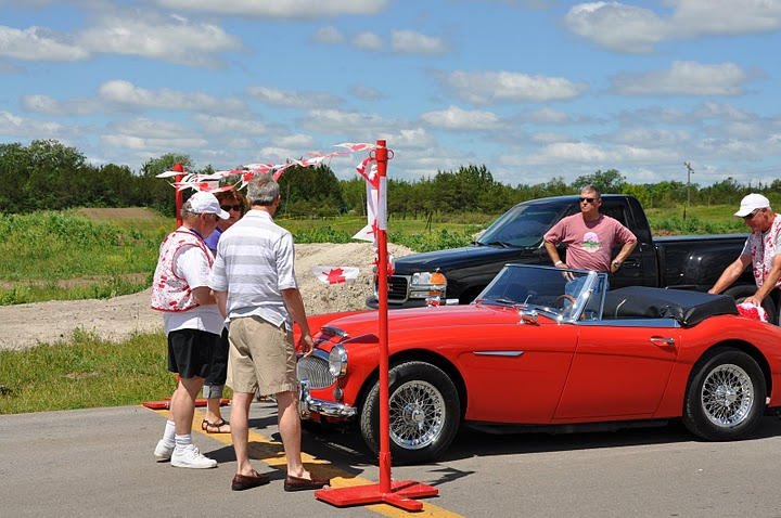 Red Austin Healey moves up to starting pole as workers look on.